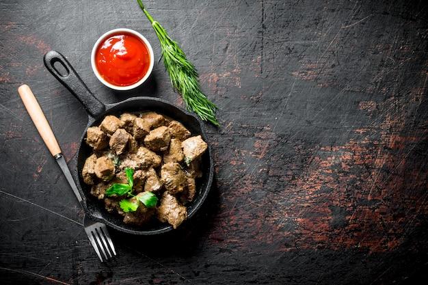 Morceaux de foie frits dans une poêle avec des herbes et de la sauce tomate. sur fond rustique foncé
