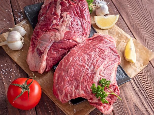 Morceaux frais et juteux de boeuf cru sur un fond en bois entouré de légumes et d'épices. vue de dessus