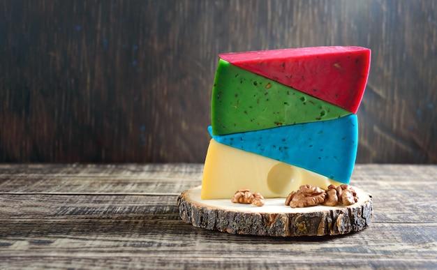 Des morceaux de fromage artisanal multicolores se trouvent dans une pile sur la table rustique.