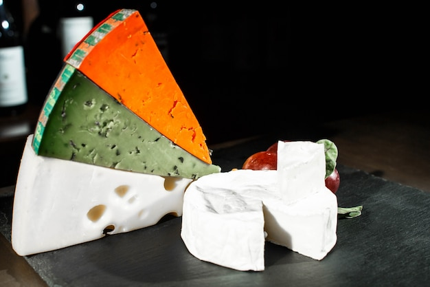 Des morceaux de fromage colorés reposent sur un plat noir