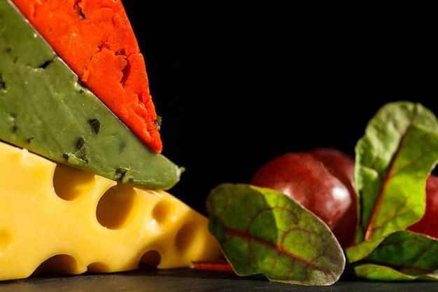Des morceaux de fromage orange, vert et suisse reposent l'un sur l'autre sur une assiette avec du raisin