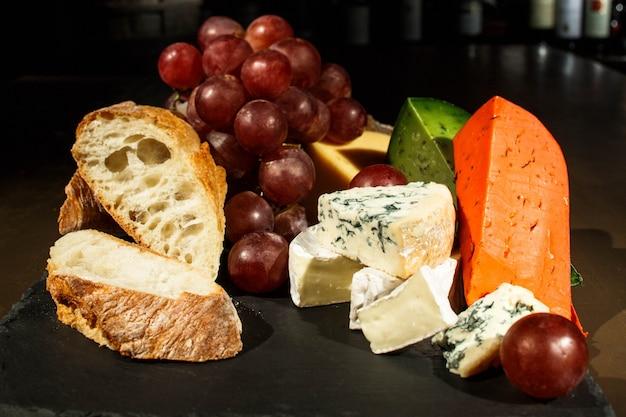 Des morceaux de fromage et de pain sur plat noir