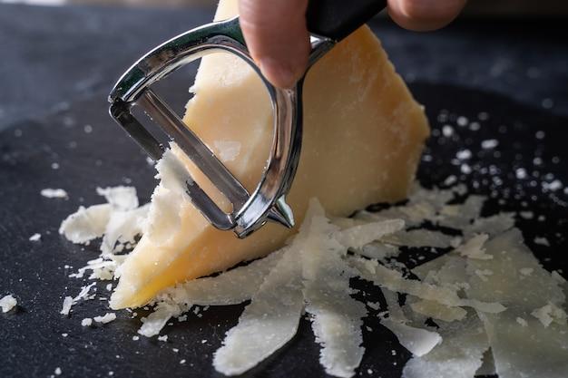 Morceaux de fromage parmesan et couteau sur table en bois noir.