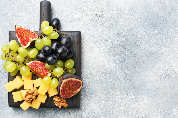 Morceaux de fromage, raisins de figues de fruits frais, miel et noix sur une planche à découper en bois. fond