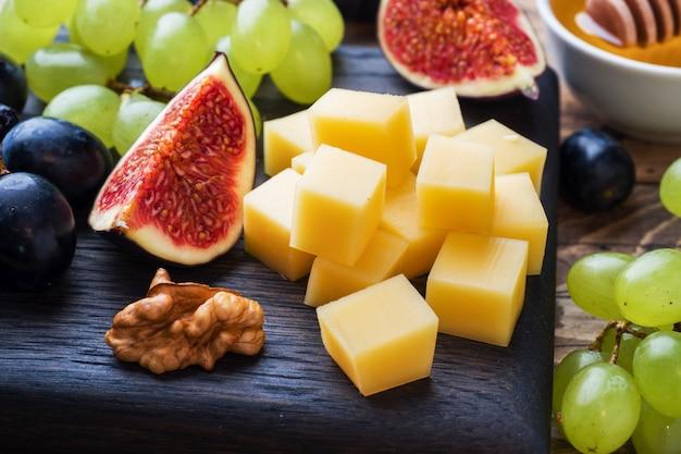 Morceaux de fromage, raisins de figues de fruits frais, miel et noix sur une planche à découper en bois. mise au point sélective. fermer.