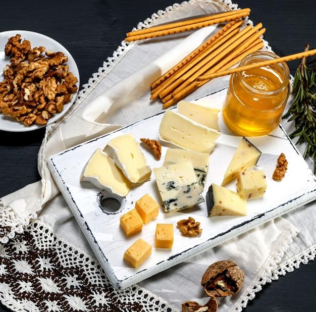 Morceaux de fromages différents sur une planche de bois blanche près d'un pot avec du miel