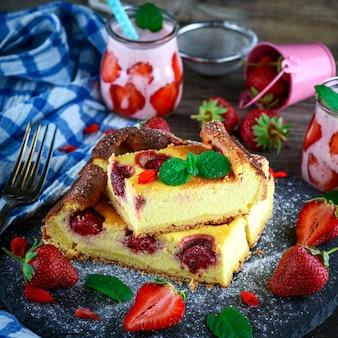 Morceaux de gâteau au fromage aux fraises sur une plaque de graphite noir