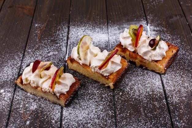 Morceaux de gâteau avec des fruits couverts de sucre en poudre servi sur une table en bois