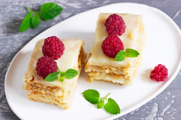 Morceaux de gâteau napoléon décorés de framboises et de feuilles de mélisse sur fond clair.
