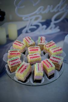 Des morceaux de gâteaux colorés servis sur un plat en verre