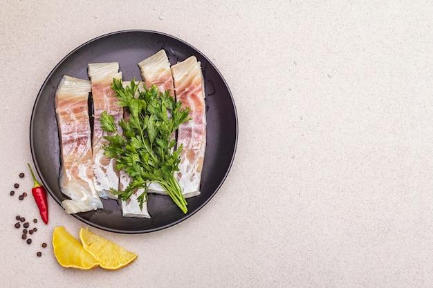 Morceaux de goberge (pollachius virens) crus. du poisson frais pour un mode de vie sain. citron, persil, sel de mer, piment, poivre noir