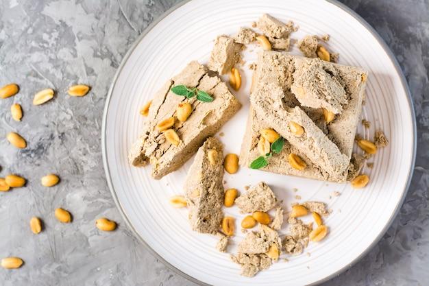 Morceaux de halva de tournesol et d'arachide et feuilles de menthe sur une assiette et noix à proximité sur la table. délicatesse orientale calorique. vue de dessus. fermer