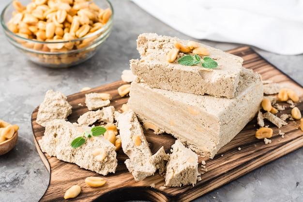 Morceaux de halva de tournesol et d'arachide et feuilles de menthe sur une planche à découper et un bol de noix sur la table. dessert oriental calorique. fermer