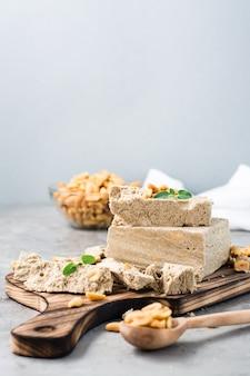 Morceaux de halva de tournesol et d'arachide et feuilles de menthe sur une planche à découper sur la table. dessert oriental calorique. vue verticale