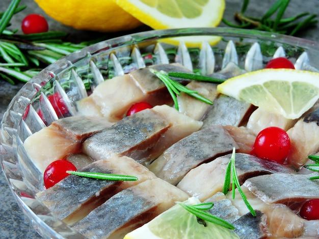 Morceaux de hareng dans un plat en cristal. canneberge, citron et romarin. hareng norvégien