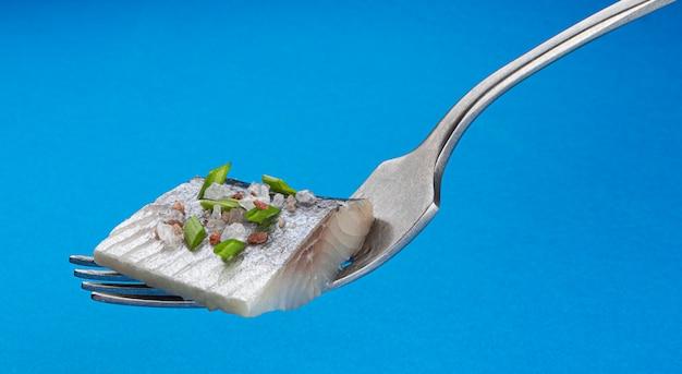 Morceaux de hareng salé sur fourche isolé sur fond bleu, tranches de filet de poisson maquereau mariné avec oignon vert coupé