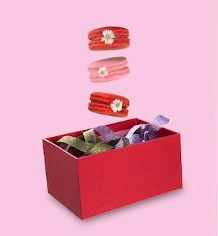Morceaux de macarons colorés ou macarons français lévitant sur une boîte cadeau rouge remplie de rubans colorés. isolement sur fond rose. photographie culinaire en lévitation.