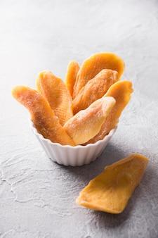 Morceaux de mangue déshydratés et séchés dans un bol blanc close up