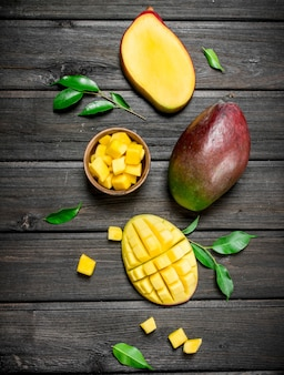 Morceaux de mangue fraîche dans un bol. sur bois noir