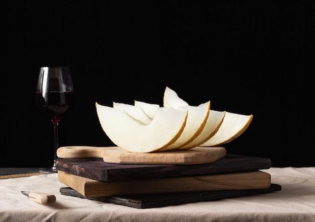 Morceaux de melon sur une planche de bois, un verre de vin en arrière-plan. style rustique.
