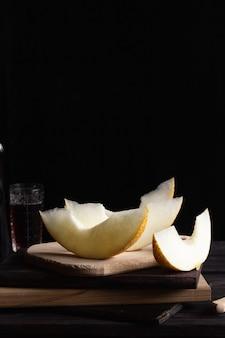 Morceaux de melon sur des planches de bois avec un couteau. style rustique.