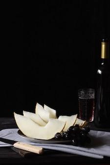 Morceaux de melon sur des planches de bois avec un couteau, un verre de vin en arrière-plan. style rustique.