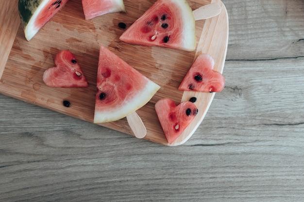 Morceaux mûrs de pastèque sur planche de bois dans la cuisine