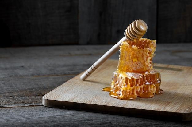 Morceaux de nid d'abeille frais avec du miel et un bâton en bois