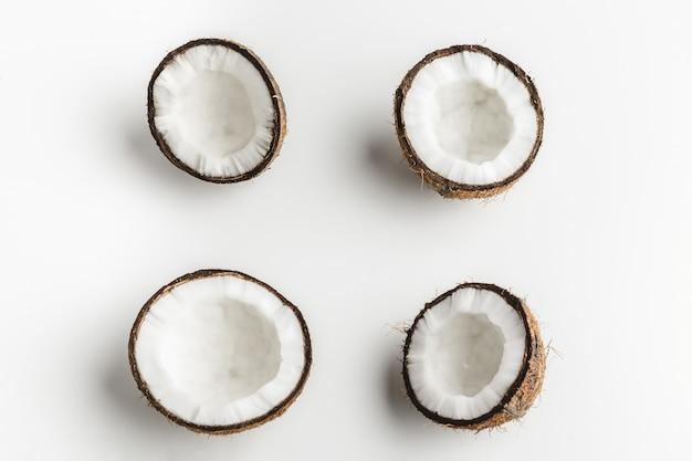 Morceaux de noix de coco mûres sur fond blanc, espace de copie