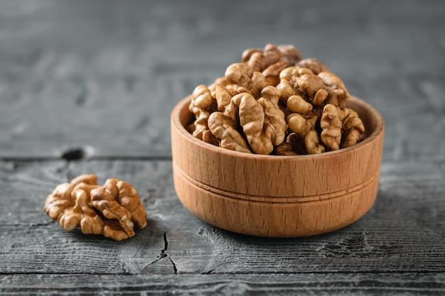 Morceaux de noix pelées dans un bol en bois sur une table en bois foncé.