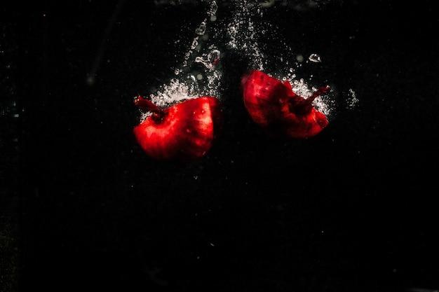 Les morceaux d'oignon rouge tombent dans l'eau sur fond noir