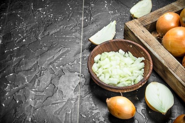 Morceaux d'oignons dans le bol et un oignon entier sur le plateau. sur rustique