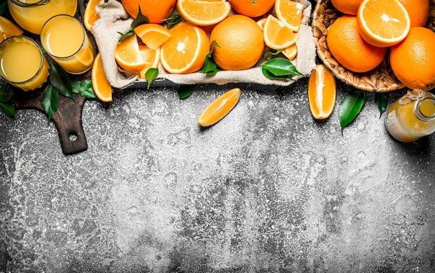 Morceaux d'oranges hachées dans une boîte avec des feuilles vertes sur fond rustique