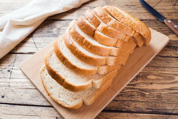 Morceaux de pain blanc pour les toasts sur une table en bois.