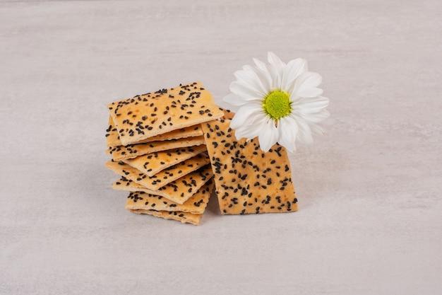 Morceaux de pain croustillant aux graines de sésame noir sur blanc avec fleur.