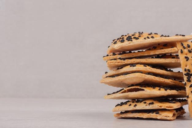 Morceaux de pain croustillant aux graines de sésame noir sur blanc.