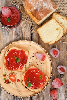 Des morceaux de pain avec une délicieuse confiture de fraises sont décorés de feuilles de menthe. table rustique en bois. confiture de fraises sucrée sur la table, vue du dessus.
