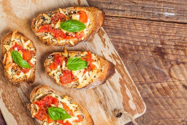 Des morceaux de pain avec du fromage et tomate