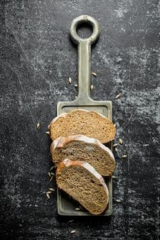 Morceaux de pain avec des grains sur la planche à découper. sur rustique foncé