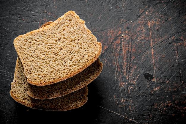 Morceaux de pain parfumé. sur une surface rustique sombre