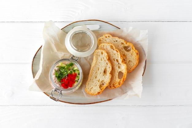 Morceaux de pain avec pâté de poisson sur table en bois blanc