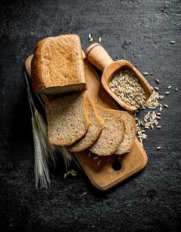 Morceaux de pain sur une planche à découper avec des épillets et du grain. sur une surface rustique noire
