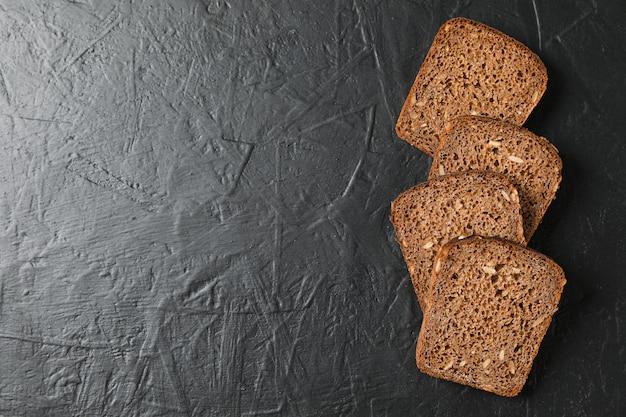 Morceaux de pain de seigle sur l'espace noir, vue de dessus et espace pour le texte