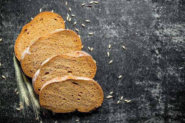 Morceaux de pain de seigle frais avec des céréales et des épillets. sur rustique foncé