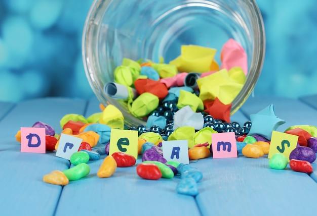 Des morceaux de papier éparpillés et des pierres colorées avec des rêves dans un vase en verre sur une table en bois bleue sur fond bleu
