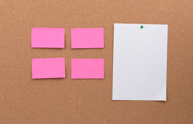 Des morceaux de papier vierges roses et blancs épinglés sur un panneau de liège, copiez l'espace