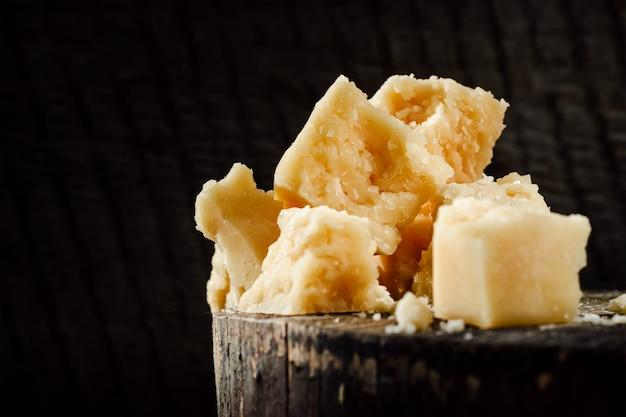 Morceaux de parmesan sur un fond en bois sombre.
