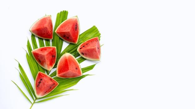 Morceaux de pastèque coupés sur des feuilles de palmier sur une surface blanche