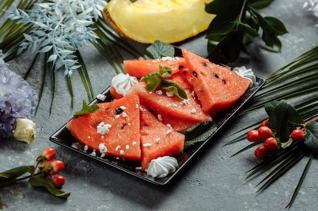 Morceaux de pastèque rouge fraîche sur une plaque noire