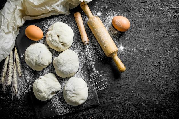 Morceaux de pâte ronds avec des œufs et un rouleau à pâtisserie